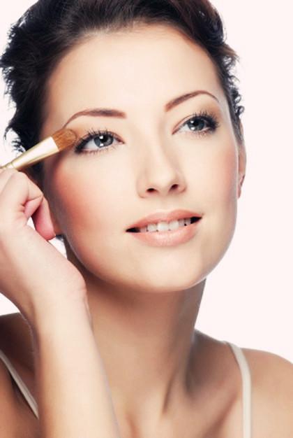 Portrait of beauty young caucasian woman applying eyeshadow on eyelid